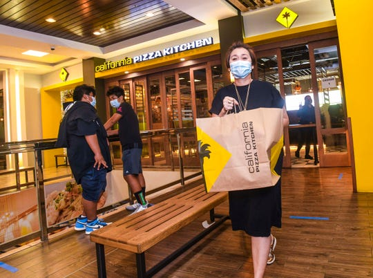 A customer carries out her order, just picked up at the California Pizza Kitchen restaurant, in Tumon on May 12, 2020. The eatery just reopened for business on Tuesday to accept takeout orders, after temporarily closing its doors on March 22, due in part to restrictions set in place to address the coronavirus pandemic.