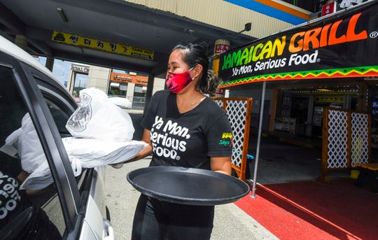 Cashier/server Bianca Retuyan sports a smile behind her mask as she delivers a customer's order during a curbside service at the Jamaican Grill Restaurant in Tumon on Tuesday, May 12, 2020.