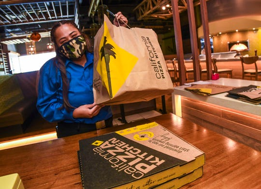 California Pizza Kitchen hostess Mariah Vuelban prepares to hand a customer their order placed with the Tumon restaurant on May 12, 2020. The eatery just reopened for business on Tuesday to accept takeout orders, after temporarily closing its doors on March 22, due in part to restrictions set in place to address the coronavirus pandemic.