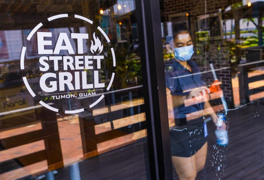 Hostess Angela Diaz cleans the front window of the Eat Street Grill after the Tumon eatery reopened for business to accept takeout orders on Tuesday, May 12, 2020. The restaurant closed the location temporarily on March 18 after restrictions were set in place due to the coronavirus pandemic.