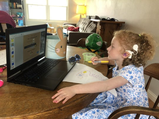 Olive, 4, does school work remotely from her home in Iowa City. Because Olive is hard of hearing, she often carefully considers facial expressions when interpreting those around her. Her parents are currently trying to figure out how to communicate effectively while still wearing facemasks in public.