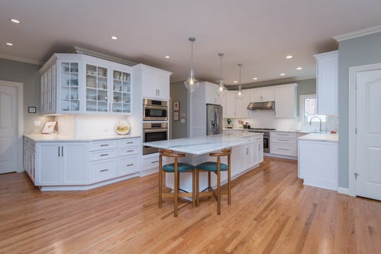 This kitchen renovation in Prospect features a large marble island with seating, ample counter space, stainless steel appliances and floating glass pendants.