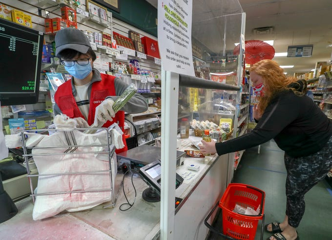 James Cook helps Rachel Batt as she checks out at Choi's Asian Food Market in Lyndon on Tuesday, May 12, 2020.