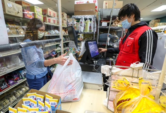 Jongin Choi helps Karen Huff check out at Choi's Asian Market in Lyndon on Tuesday, May 12, 2020.
