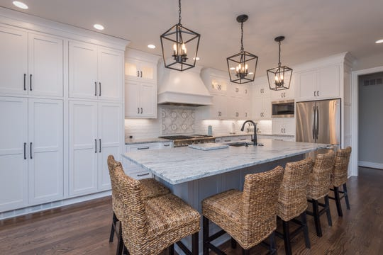 This kitchen renovation in Windy Hills features a large marble island with seating for six, ample cabinet and storage space, a high-end gas range and stainless steel appliances.