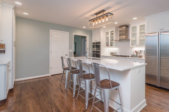 This kitchen renovations in Maryhill Estates features a large island with seating for four, a gas range, stacked ovens and clean, crisp lines.