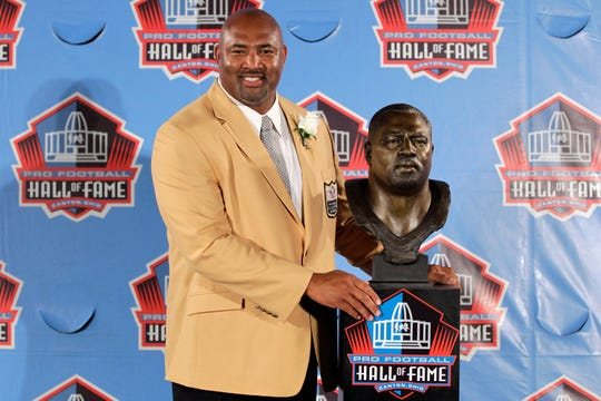 Former NFL player Dermontti Dawson poses with a bust of himself during an induction ceremony at the Pro Football Hall of Fame, Saturday, Aug. 4, 2012, Saturday, Aug. 4, 2012, in Canton, Ohio. (AP Photo/Gene J. Puskar)