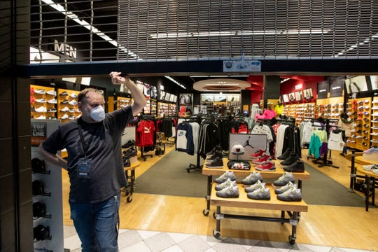 Sales Manager Shawn Densmore holds the gate at Foot Locker inside Oak Court Mall, where they are limiting the store to 50% capacity on its second day after reopening Tuesday, May 12, 2020.