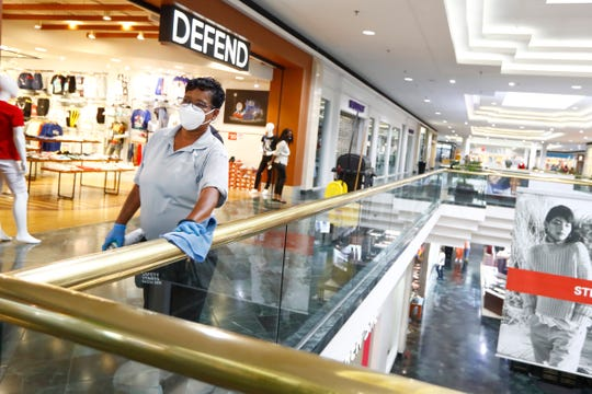 Sheldra Knox works to disinfect the hand rails at Oak Court Mall on its second day after reopening Tuesday, May 12, 2020.