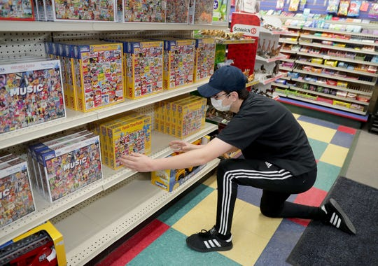 Employee Jack Stuhlmacher adjusts some puzzles on a shelf at Winkie's Toys and Variety in Whitefish Bay, which is among the area businesses that have reopened.