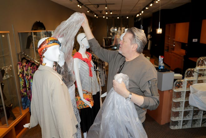 Michael Kruczynski, owner of New Options Salon and Boutique, removes protective plastic from mannequins shortly after reopening his shop  on East Silver Spring Drive in Whitefish Bay on Tuesday.  As of May 11, standalone or strip mall-based retail stores can offer in-person shopping, as long as customers are limited to five at a time and social-distancing guidelines are followed, Gov. Tony Evers announced Monday.