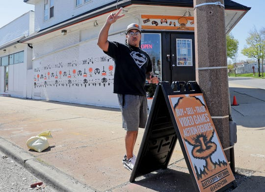 Bryant Wilcox, Battlebox Studios co-owner, waves to a motorist blowing their horn while he puts out a sign after reopening the family-owned gaming store at 5431 W. Lisbon Ave. in Milwaukee on Tuesday, May 12, 2020.  As of May 11, standalone or strip mall-based retail stores can offer in-person shopping, as long as customers are limited to five at a time and social-distancing guidelines are followed, Gov. Tony Evers announced Monday.