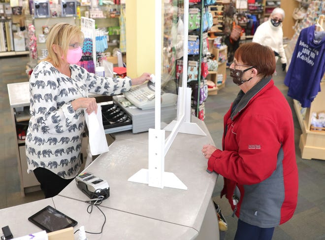 Winkie's co-owner Julie Stuhlmacher, left, assists customer Janice Kocinski at Winkie's Hallmark and Gifts in May. The Whitefish Bay Village Board unanimously voted on Thursday to require face masks in all buildings open to the public when social distancing is not possible.