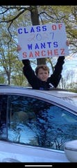 A child holds a sign supporting tenure for Mountain Lakes High School Principal Frank Sanchez. May 9, 2020