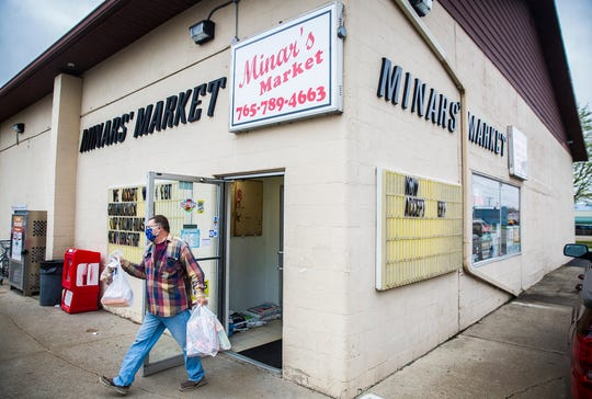 A customer wearing a surgical mask exits Minars Market in Albany.