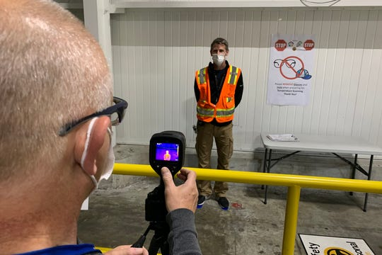Todd Haylett, facilities manager, has his temperature measured by George Sylvester, manufacturing engineering manager, at the General Motors assembly plant in Spring Hill, Tenn., on Monday, May 11, 2020. The day marked the return of the first group of team members to the plant following shutdown to prevent the spread of the coronavirus.