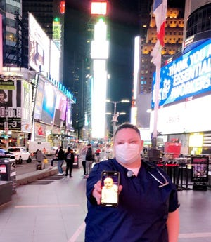 Genesis Hospital registered nurse Micki Gross of Newark displays a picture of her daughter, Karter, at Times Square in New York City, where she recently worked on the frontlines of the COVID-19 pandemic.
