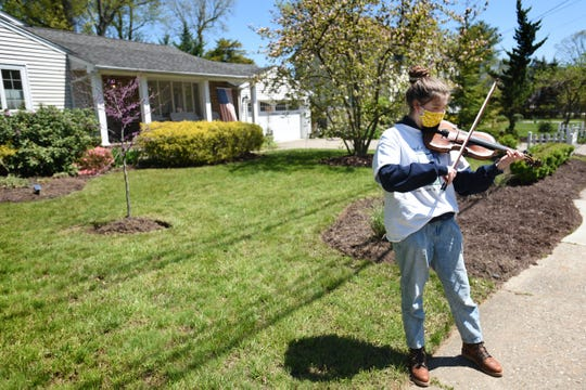 Claudia Mejia-Sydenstricker, a member of Wind of the Spirit, plays a violin outside of the home of Assemblyman Robert Auth, in protest of the 39th legislative district representative's recent dismissal of working class and immigrant New Jerseyans' pleas for COVID19 Relief during an assembly hearing last week, photographed in Old Tappan on 05/12/20.