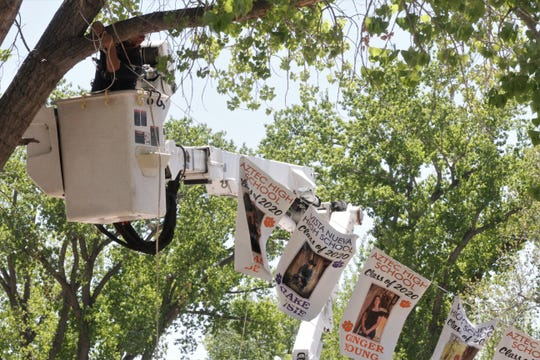 An Aztec electric utility worker hangs banners showing pictures of graduating seniors.