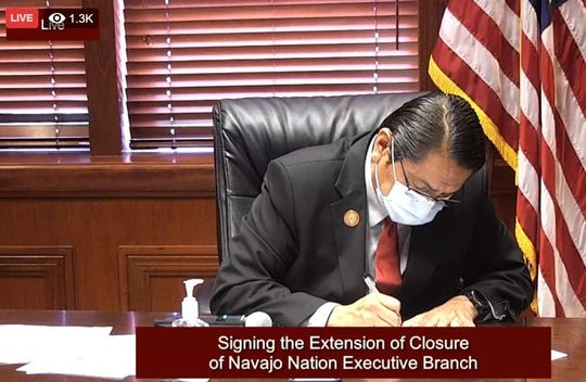 A screenshot shows Navajo Nation President Jonathan Nez signing a new executive order to keep the executive branch closed in a live stream on Facebook on May 12.