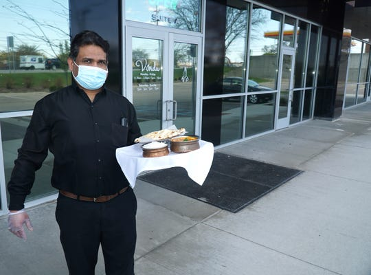 Vindu restaurant employee Rajeev Malgi holds a lunchtime meal of butter chicken, rice and naan bread. The Farmington eatery received approval from the planning commission to establish some outdoor seating at its Grand River Avenue location.