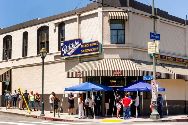 FILE - In this Saturday, May 2, 2020, file photo, people stand in line while following social distancing guidelines as they wait for French dip sandwiches outside Philippe the Original restaurant in downtown Los Angeles. Struggling California restaurants are awaiting word on when they can reopen and many are preparing to provide new safety measures against the coronavirus. Gov. Gavin Newsom is expected Tuesday to provide more details of what's required before his plan to reopen California's economy reaches restaurant dining rooms that have been shuttered since mid-March. (AP Photo/Damian Dovarganes, File)