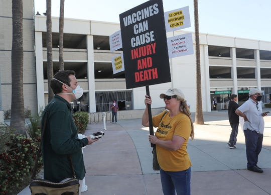 Desert Sun reporter Sam Metz talks with a anti-vaccine protester Tara Madsen at the Riverside County Administration Center, May 5, 2020.