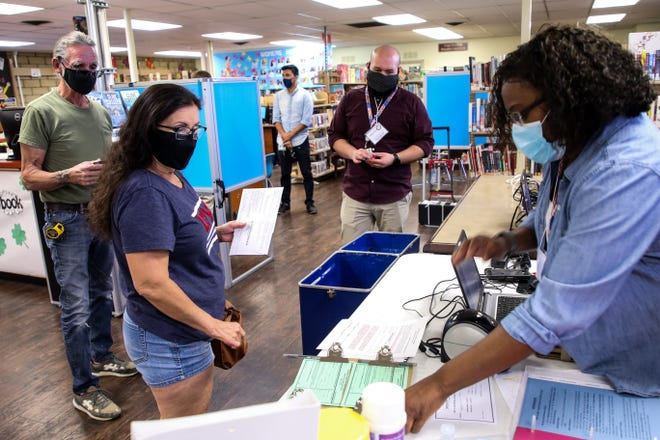 Thom Trollope and Frankie Trollope work with Riverside County elections technician, Tralyn Davis, at the Desert Hot Springs Library voting location to drop off their ballots for the special election for state senate on Tuesday, May 12, 2020 in Desert Hot Springs, Calif.