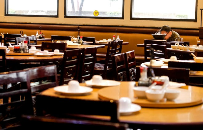 FILE - In this March 12, 2020, file photo, a diner eats lunch at a restaurant in Rosemead, Calif. Struggling California restaurants are awaiting word on when they can reopen and many are preparing to provide new safety measures against the coronavirus. Gov. Gavin Newsom is expected Tuesday, May 12, to provide more details of what's required before his plan to reopen California's economy reaches restaurant dining rooms that have been shuttered since mid-March. (AP Photo/Ringo H.W. Chiu, File)