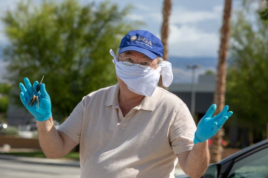 Desert Sun golf writer Larry Bohannan gestures to a colleague after doing some news gathering in Indio, Calif., on April 8, 2020.