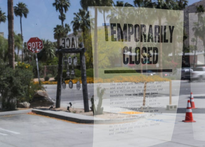 A sign posted at the lobby of the Ace Hotel tells the public of the hotel's closure due the coronavirus in Palm Springs, May 8, 2020.