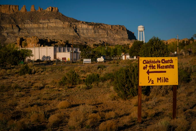 A hand-painted sign points the way to the Chilchinbeto Church of the Nazarene in Chilchinbeto, Ariz., on the Navajo reservation at sunrise on Sunday, April 19, 2020. The Navajo reservation has some of the highest rates of coronavirus in the country. If Navajos are susceptible to the virus' spread in part because they are so closely knit, that's also how many believe they will beat it. (AP Photo/Carolyn Kaster)