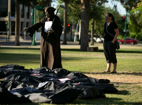 An individual dressed as the Grim Reaper and Tanya Luken of Phoenix, stand alongside dozens of pretend body bags during a rally to pressure the governor to not open the state up too quickly during the COVID-19 pandemic, at the Arizona state Capitol in Phoenix on May 12, 2020.