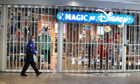 A TSA agent walks past the Magic of Disney store, which is still closed in response to the coronavirus crisis, at Orlando International Airport, Thursday, May 7, 2020. Airport passenger traffic continues to be light in the second month of the pandemic response. (Joe Burbank/Orlando Sentinel/TNS)