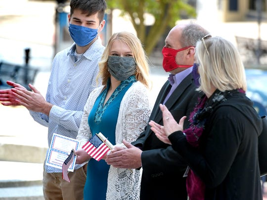 Paul Barlow and his daughter Paige, 18, center, of Dallastown, are applauded by Paige's boyfriend Seth Balderston, left, and Paul's fiancee Erika Winemiller during a naturalization ceremony on the steps of the York County Administrative Center Tuesday, May 12, 2020. The Barlows originating country is the United Kingdom. They and 4 others became U.S. citizens during the event. Bill Kalina photo