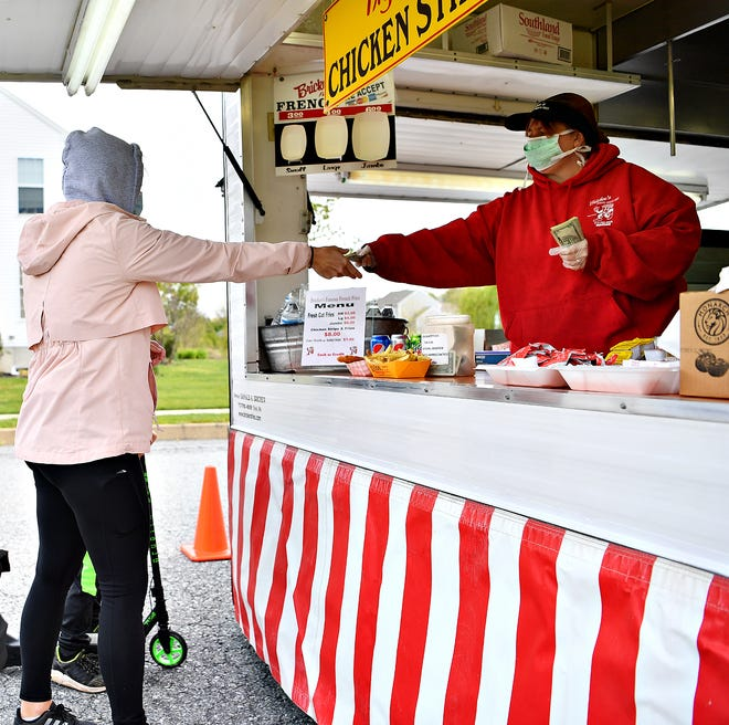 Abby Leiphart, left, of York Township, is served by Cynthia Walker, of Bricker's French Fries as the food truck makes a stop in the neighborhood of Sage Hill in York Township, Saturday, May 9, 2020. Dawn J. Sagert photo