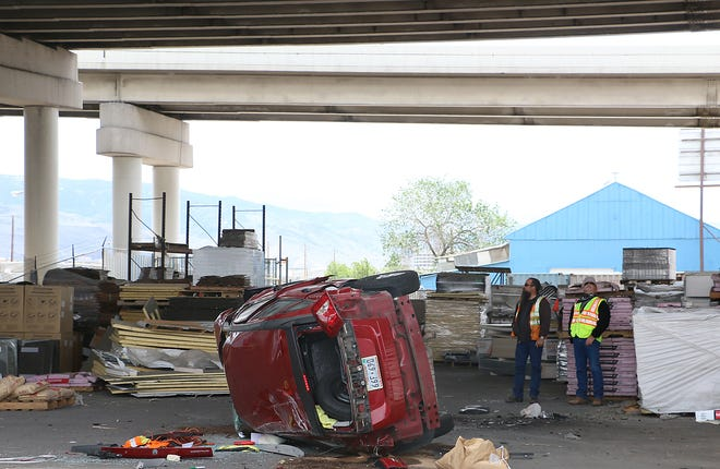 NDOT employees survey the scene where a car that fell off the I-580 freeway and landed on the property of Roofline Supply and Delivery near the spaghetti bowl in Reno on May 12, 2020.