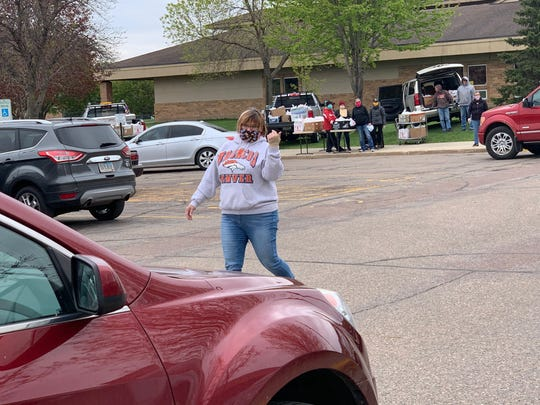 School district nutrition director Gay Anderson directs traffic at Brandon Valley elementary school on Tuesday, May 12, 2020 for the free lunch program.