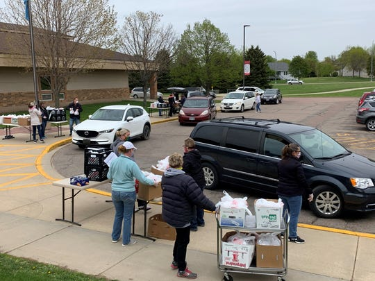Cars line up at the Brandon Valley elementary school as workers distribute the free lunch program on Tuesday, May 12, 2020.