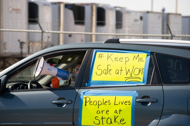Patty Keeling, vice president of Asamblea de Derechos Civiles, lead chants with a megaphone from inside her car parked outside the Pilgrim's Pride poultry-processing plant Monday, May 11, 2020, in Cold Spring.