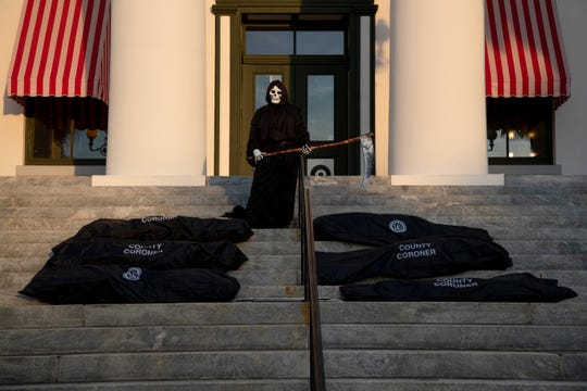 A protestor dressed as the Grim Reaper stands at the steps of the Florida Historic Capitol while four others line body bags at its feet, representing the lives of Floridians who have or who may die from COVID-19 during a protest urging Gov. Ron DeSantis not to rush to re-open the state Tuesday, May 12, 2020.