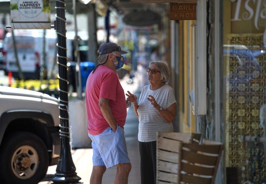 """Ken Parvin (left), and his wife Joan, of Jensen Beach, stop to chat while window shopping along Southwest Osceola Street on May 12 in downtown Stuart. """"I wear a mask because I think I'm saving you, protecting you from the coronavirus, and I'm just trying to follow the regulation, and what has been recommended,"""" Ken Parvin said."""