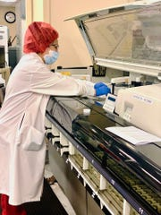 Gina Olaes, a clinical laboratory scientist, runs a test at St. John's Regional Medical Center.
