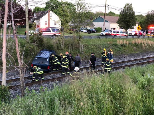 First responders assist a person trapped in a vehicle that went off the road, down an embankment and on to the railroad tracks near the Boulevard and Walnut Road.. May 11, 2020.