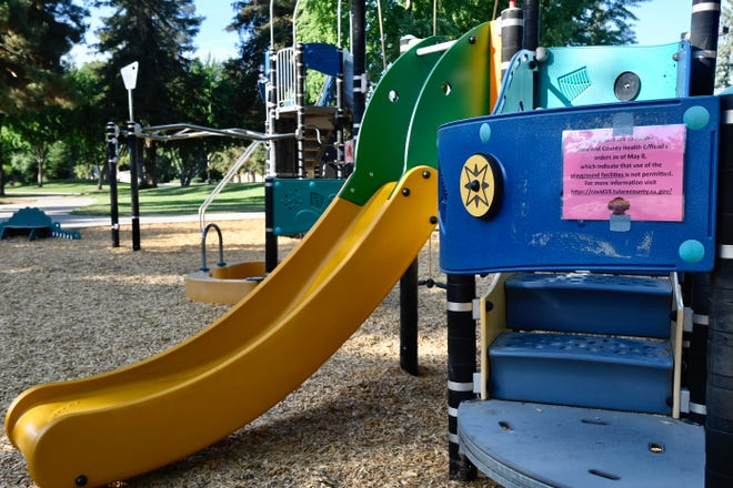 Signs at Visalia's Blain Park warn residents that use of playgrounds is not permitted under current health orders. The city re-closed playgrounds and arbors less than one week after opening them to the public.