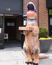 T. rex holding Lucio's pizza in Pleasantville