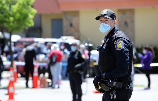 Yonkers Police Officer Ricardo Clerigo looks on as residents wait in line for free masks and gloves at the Lincoln Park distribution site in South Yonkers May 12, 2020.