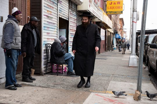 FILE - In this Dec. 13, 2019, file photo, a Jewish man, right, walks along Martin Luther King Drive in Jersey City, N.J., near the location where three people and two gunmen were shot and killed earlier in the week. American Jews were targets of more anti-Semitic incidents in 2019 than any other year over the past four decades, a surge marked by deadly attacks on a California synagogue, a Jewish grocery store in New Jersey and a rabbi's New York home, the Anti-Defamation League reported Tuesday, May 12.