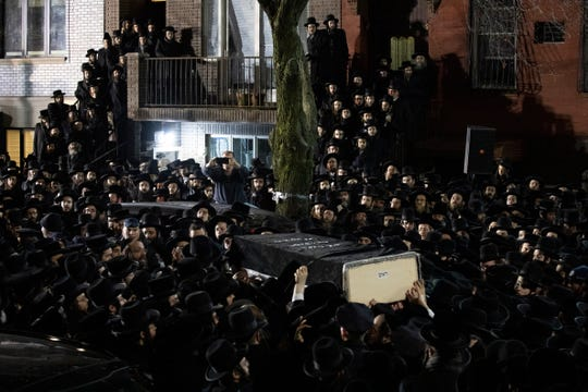 FILE - In this Dec. 11, 2019, file photo, Orthodox Jewish men carry Moshe Deutsch's casket outside a Brooklyn synagogue following his funeral in New York. Deutsch was killed in a shooting inside a Jersey City, N.J., kosher food market. Authorities said the attackers, David Anderson and Francine Graham, were motivated by a hatred of Jewish people and law enforcement. (AP Photo/Mark Lennihan, File)