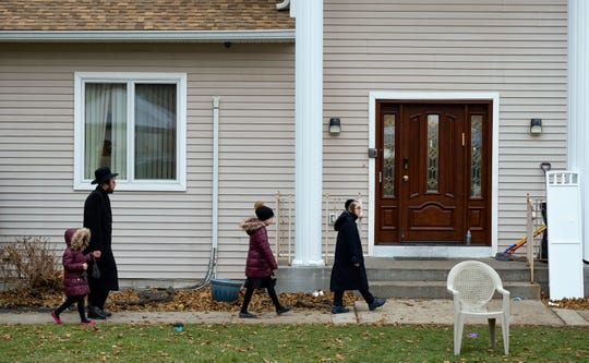 FILE - In this Dec. 29, 2019, file photo, community members walk in front of a rabbi's residence in Monsey, N.Y., following a stabbing the night before during a Hanukkah celebration. Grafton Thomas, 37, was charged with stabbing five people with a machete at the rabbi's home in Monsey, an Orthodox Jewish community north of New York City. One of the five victims died three months after the Dec. 28 attack. Federal prosecutors said Thomas had handwritten journals containing anti-Semitic comments and a swastika. (AP Photo/Craig Ruttle, File)